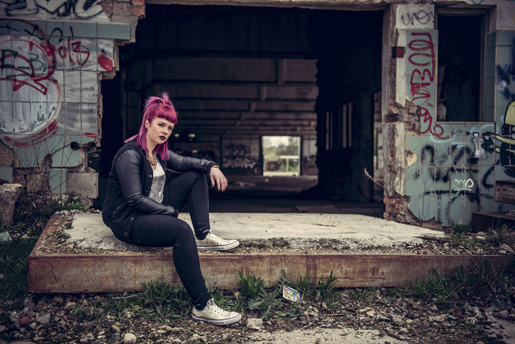 Portrait of young woman sitting by abandoned building