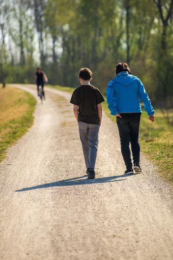 Rear view of people walking on dirt road