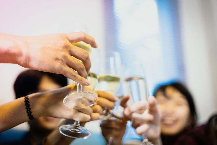 Adult Alcohol Celebratory Toast Drink Friendship Glass Group Of People Hand Holding Human Arm Human Body Part Human Hand Human Limb Indoors  Leisure Activity Lifestyles Men Real People Refreshment Smiling Women
