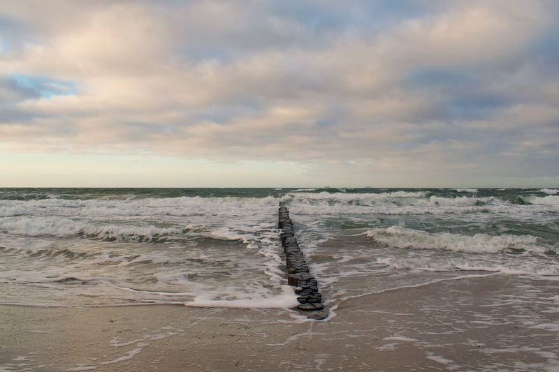 Flowing Water Outdoors Aquatic Sport Sport Non-urban Scene No People Wave Nature Tranquil Scene Tranquility Motion Land Beach Beauty In Nature Scenics - Nature Horizon Over Water Horizon Sea Water Cloud - Sky Sky Sunset Idyllic Groyne