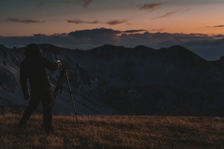 Man photographing on mountain against sky during sunrise