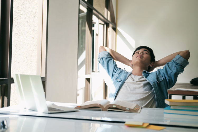Male student sleeping by table