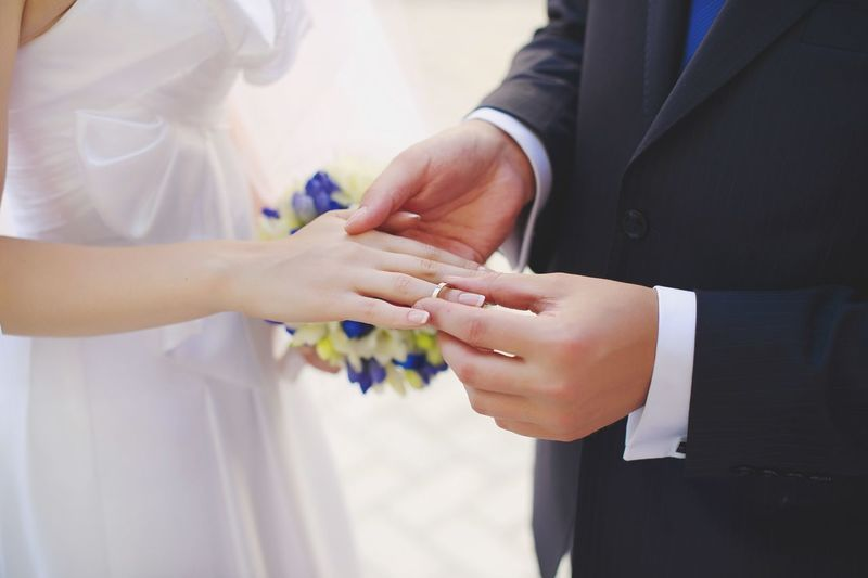 Midsection Of Bridegroom Putting Ring In Hand Of Bride