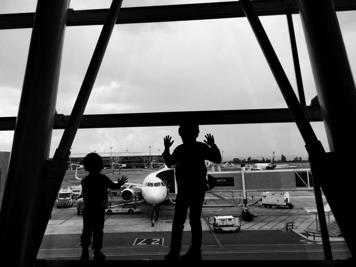 Rear view of children looking through window while standing at airport