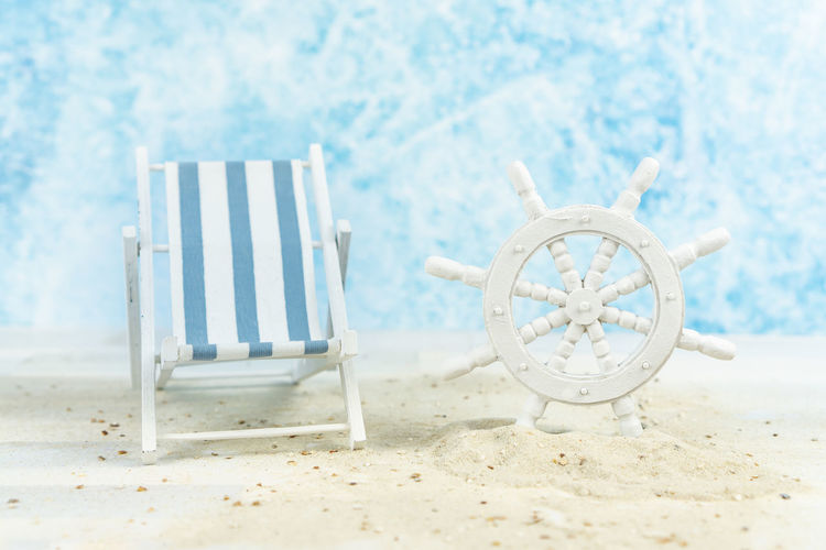 Maritime background with sand, an old white ships wheel and a blue and white striped beach chair Background Beach Chair Wheel Ship Wooden Steering White Beautiful Nature Sand Blue Summer Decoration Holiday Marine Sea Ocean Tropical Star Shell Above Maritime Copy Space Recreation  Relax Break Land Seat Day No People Water Beauty In Nature Tranquility Scenics - Nature Absence Focus On Foreground Outdoors Sunlight
