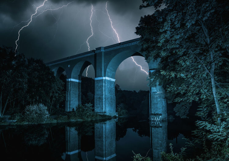 Arch bridge over river against sky at night