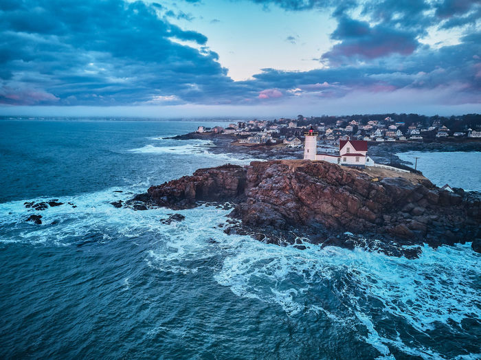 Lighthouse In Sea Against Sky At Dusk