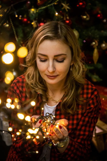 Young woman on illuminated christmas tree