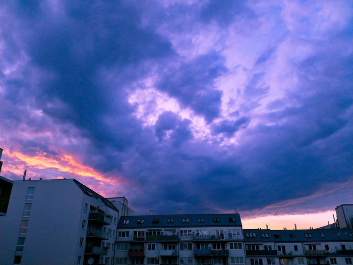 Low angle view of buildings against dramatic sky