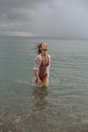 Woman wearing bikini walking in sea