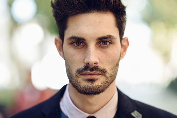 Attractive man in the street wearing british elegant suit. Young bearded businessman with modern hairstyle in urban background. Attitude Beard Beautiful People Close-up Confidence  Contemplation Facial Hair Focus On Foreground Front View Hairstyle Handsome Headshot Looking At Camera Men Mustache One Person Portrait Real People Serious Young Adult Young Men