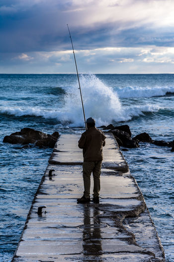 Rear view of man fishing on pier in sea against cloudy sky