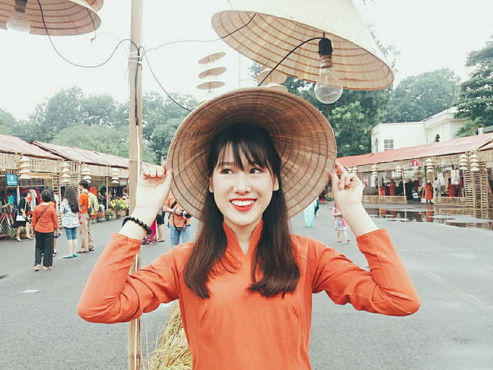 Happy woman wearing asian style conical hat at street market