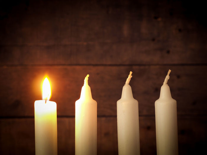 Close-up of candles against wall
