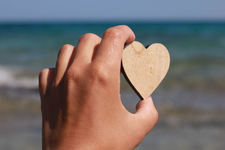 Close-up of hand holding heart shape over sea