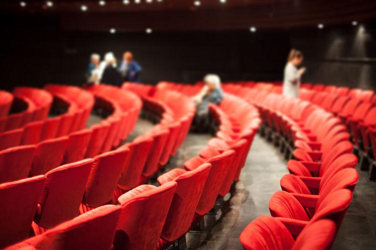 Defocused people and red chairs in auditorium