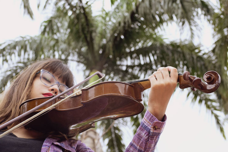Young woman playing guitar on tree