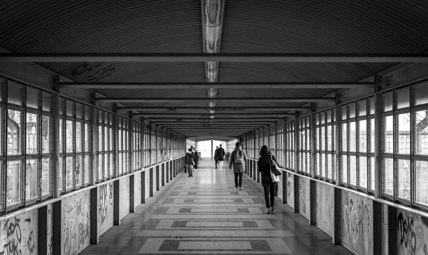 Black And White Street Photography Streetwise Photography Footbridge Architecture The Way Forward Direction Real People Built Structure Indoors  Walking Group Of People Lifestyles Ceiling Men Diminishing Perspective Railing Rear View Transportation Footpath People Leisure Activity Women Illuminated