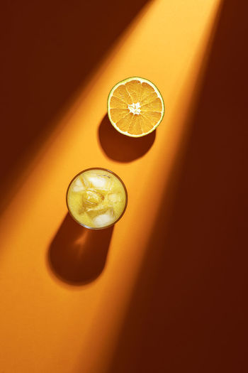 High angle view of orange by drink on table