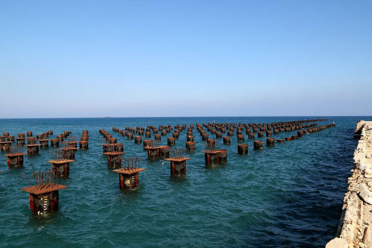 Metal in sea against blue sky