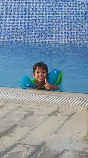 Portrait of smiling boy showing thumb up in swimming pool