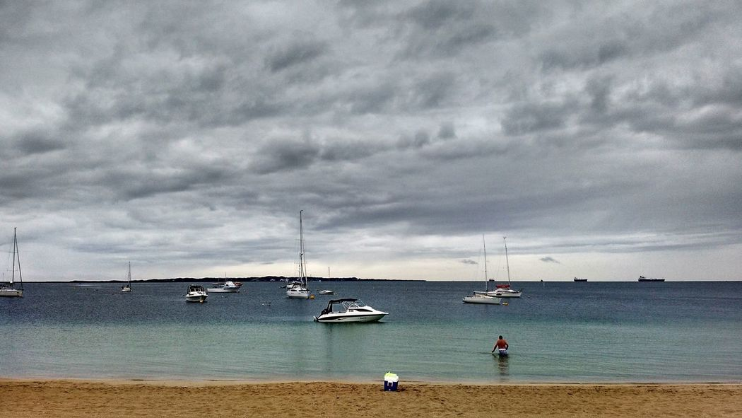 A man wades into the sea on a gray and threatening day. Melancholy Forlorn Gray Sky Overcast Stormy Boats Marina