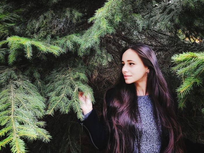 Thoughtful young woman standing against trees