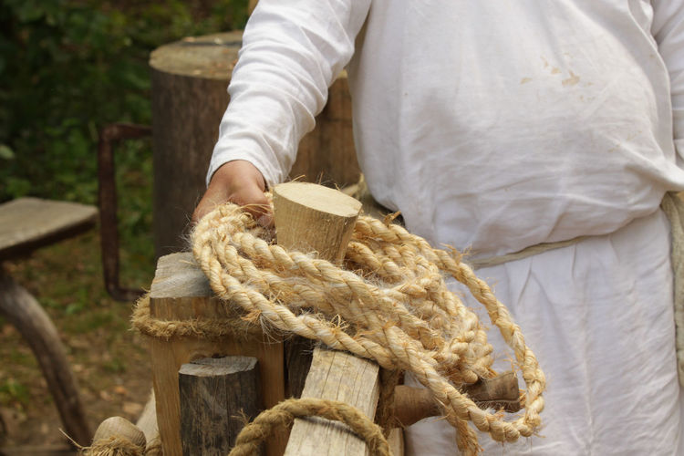 Midsection of man holding rope by railing