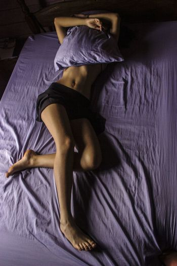 Shirtless woman lying on bed