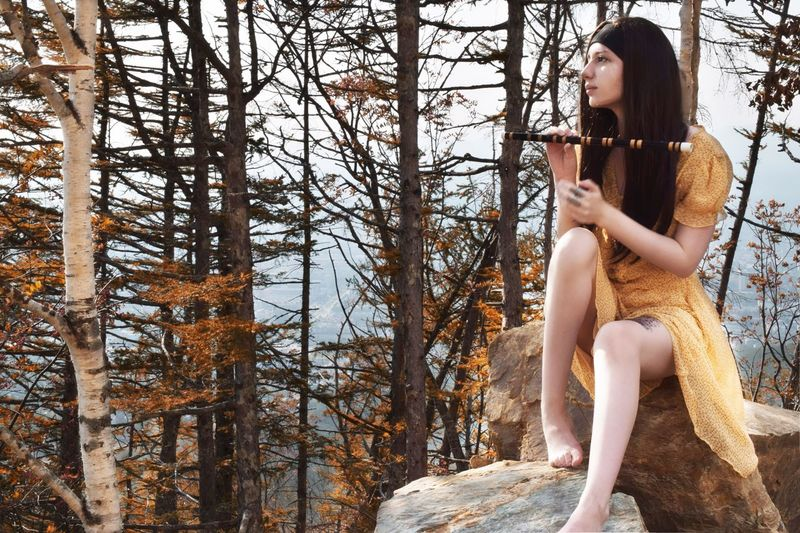 Thoughtful Woman With Flute Sitting On Rock Against Trees On Mountain