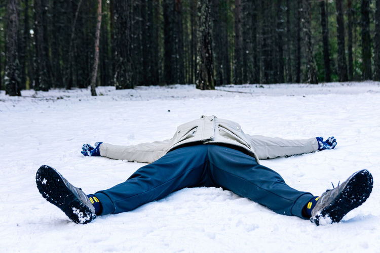 Man lying on snow covered land