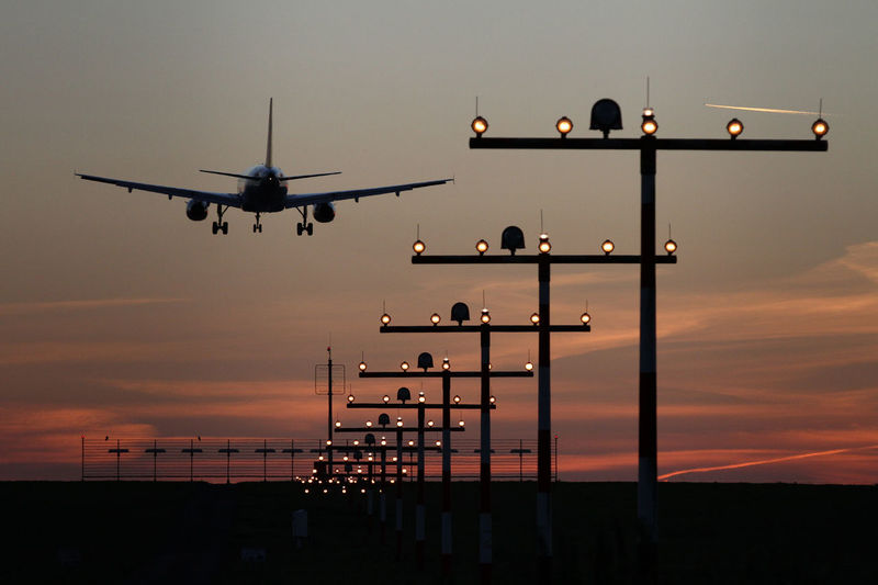 An airplane lands at the Düsseldorf Airport (Germany) during sunset. Airplane Airport Arrival Beauty In Nature Cloud Cloud - Sky Destination Flying Landing Low Angle View Mid-air Nature No People On The Move Orange Color Outdoors Scenics Sky Sunset Tranquility It's About The Journey