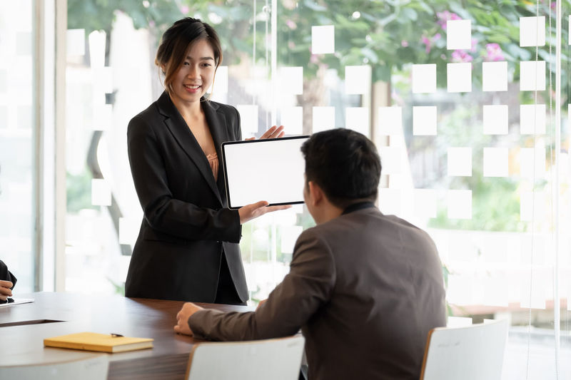 Young man working with woman standing in front of office