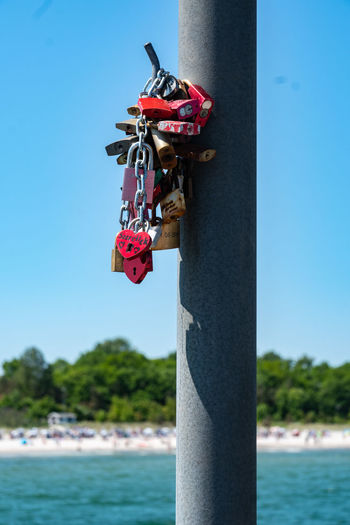 Close-up of padlocks on pole against sea