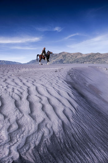 Mid adult man riding horse at desert against sky