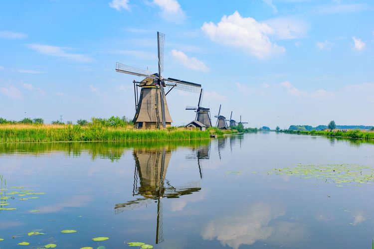 Traditional windmill on water against sky