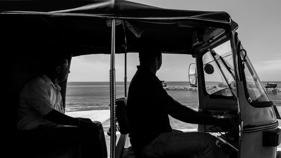 Driver and Passenger - Captivated by the Sea Beauty In Nature Black And White Casual Clothing Colombo Sri Lanka Day Feel The Journey Horizon Over Water Journey Leisure Activity Lifestyles Mode Of Transport Nature Outdoors Scenics Sea Sitting Sky Sri Lanka Strangers In Transit Tourism Tourist TukTuk Vacations Water The Street Photographer - 2018 EyeEm Awards The Traveler - 2018 EyeEm Awards Streetwise Photography The Street Photographer - 2019 EyeEm Awards