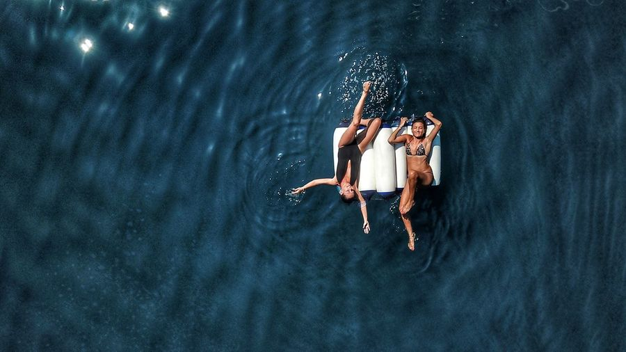 Drone View Of Friends Floating On Sea