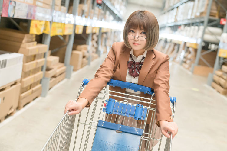 Portrait of young woman standing in warehouse