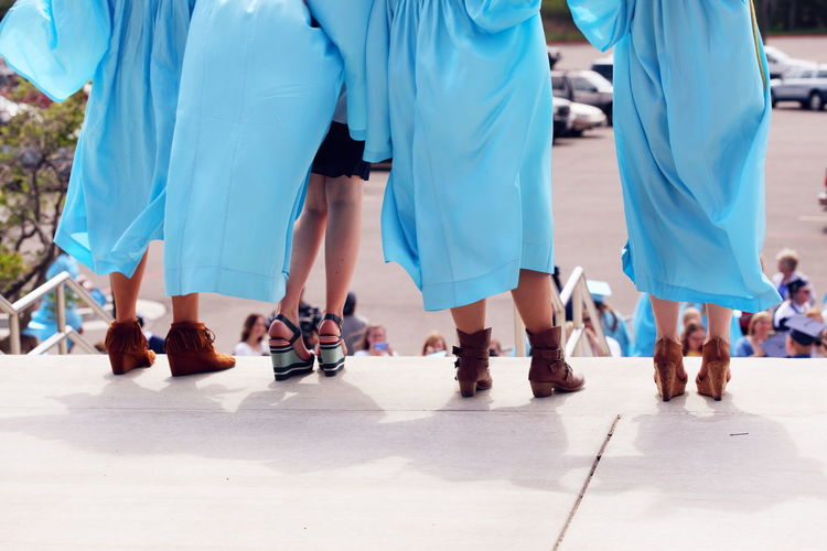 Low Section Of Women In Graduation Gown On Steps
