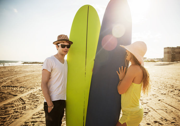 Friends with surfboards standing at beach against sky