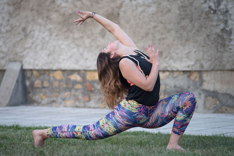 Full length of woman practicing yoga with arms raised on field