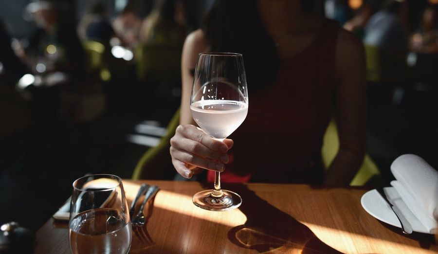 Midsection of woman holding drinking glass at restaurant