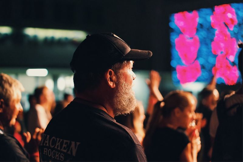 Midsection of man with arms raised at night