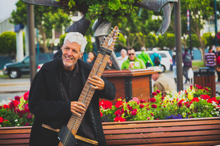 Adult Adults Only Day Flower Focus On Foreground Front View Guitar Happiness Holding Lifestyles Music Musical Instrument Musician One Person Outdoors People Performance Playing Plucking An Instrument Real People Smiling Street