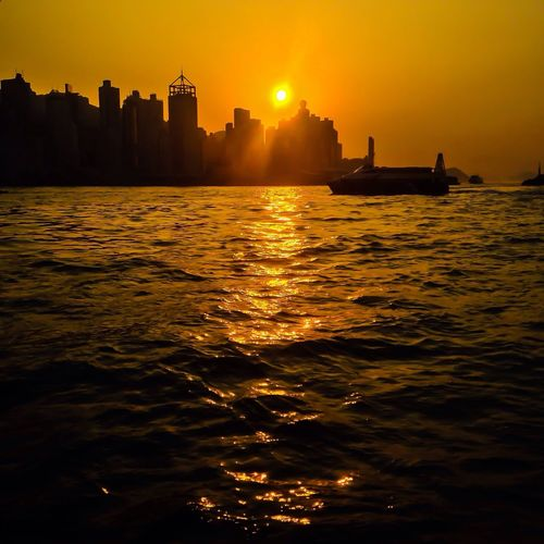 Scenic View Of Sunset Over River And Silhouette City Buildings