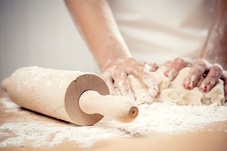 Woman kneading dough, close-up photo Cooking Culinary Homemade Housewife Knead Knead Dough Press Woman Baker Bakery Bread Caucasian Close Up Close-up Cookery Dough Female Flour Kneading Kneading Dough Pastry Rolling Pin Table Woman Hands Wooden
