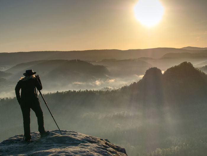 Lady photographer tourist with camera shoots sunrise while standing at tripod on top of mountain.