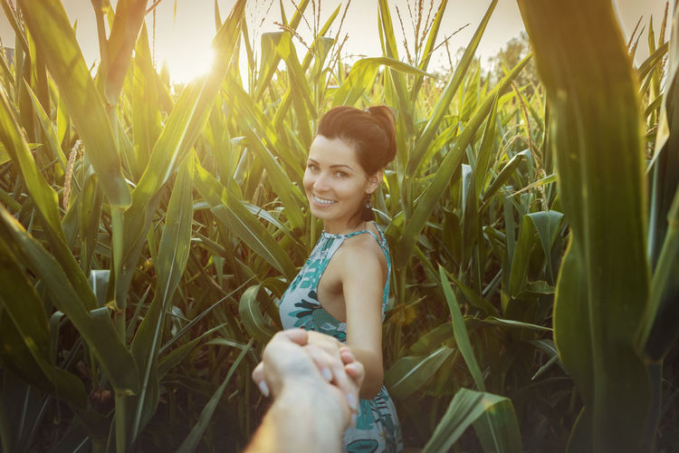 Smiling young woman standing amidst plants on field
