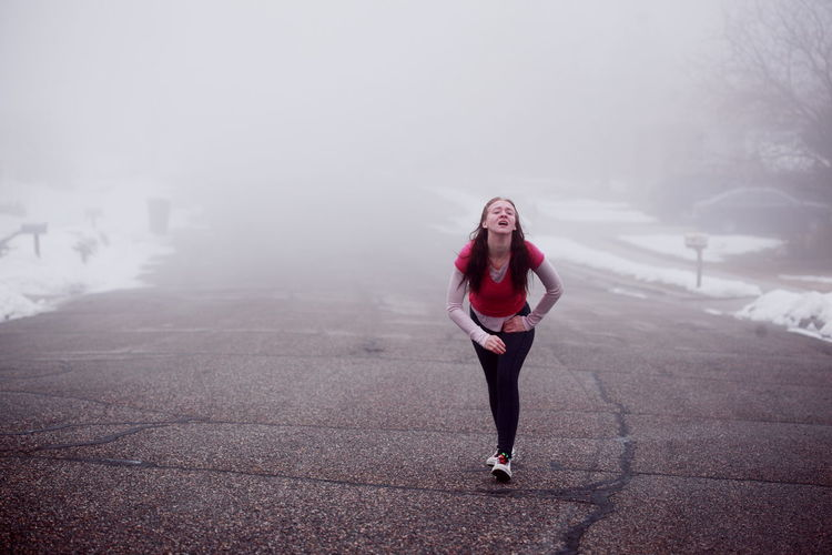 Full Length Portrait Of Tired Young Woman Walking On Road Foggy Weather